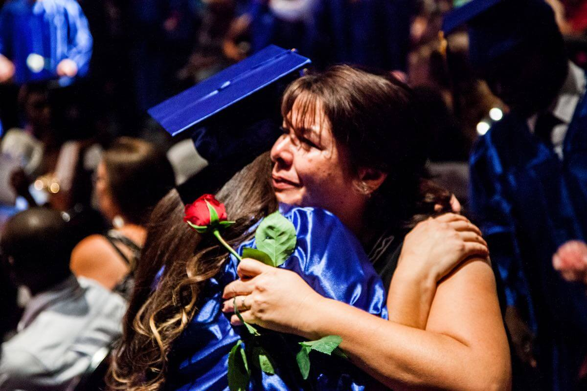 Edge High School graduate hugging person with rose