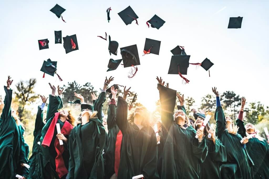 Edge High School graduates wearing gowns and tossing caps into the sky
